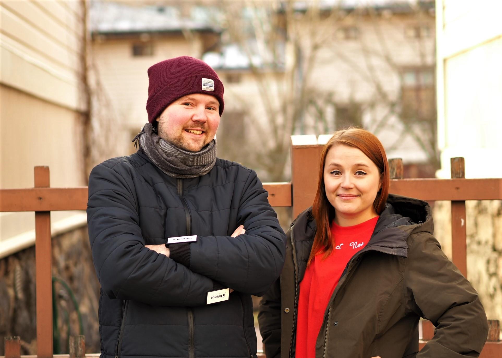 Touko ja Siiri seisovat talvivaatteet päällä puisen portin edessä aurinkoisessa säässä.