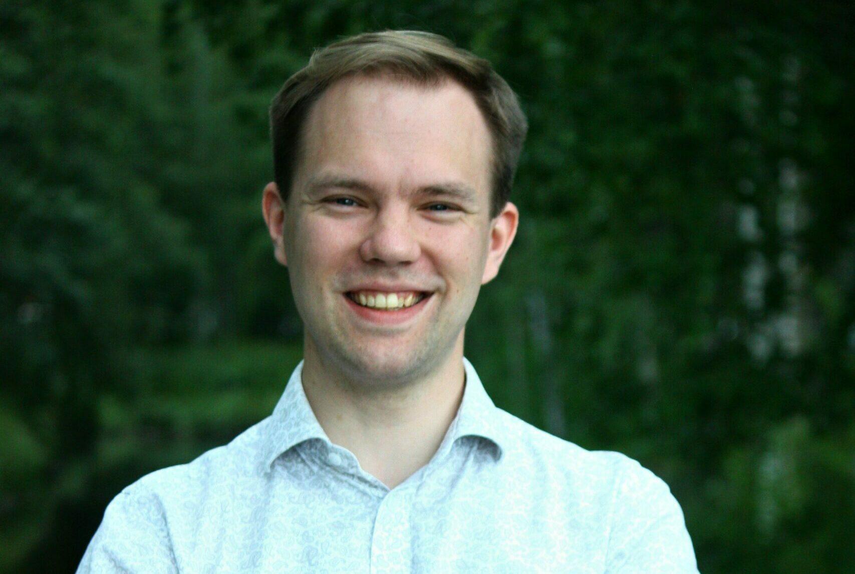 Sakari Tuomisto hymyilee kuvassa, hänellä on päällään valkoinen kauluspaita ja kädet ovat ristittynä rinnalla.