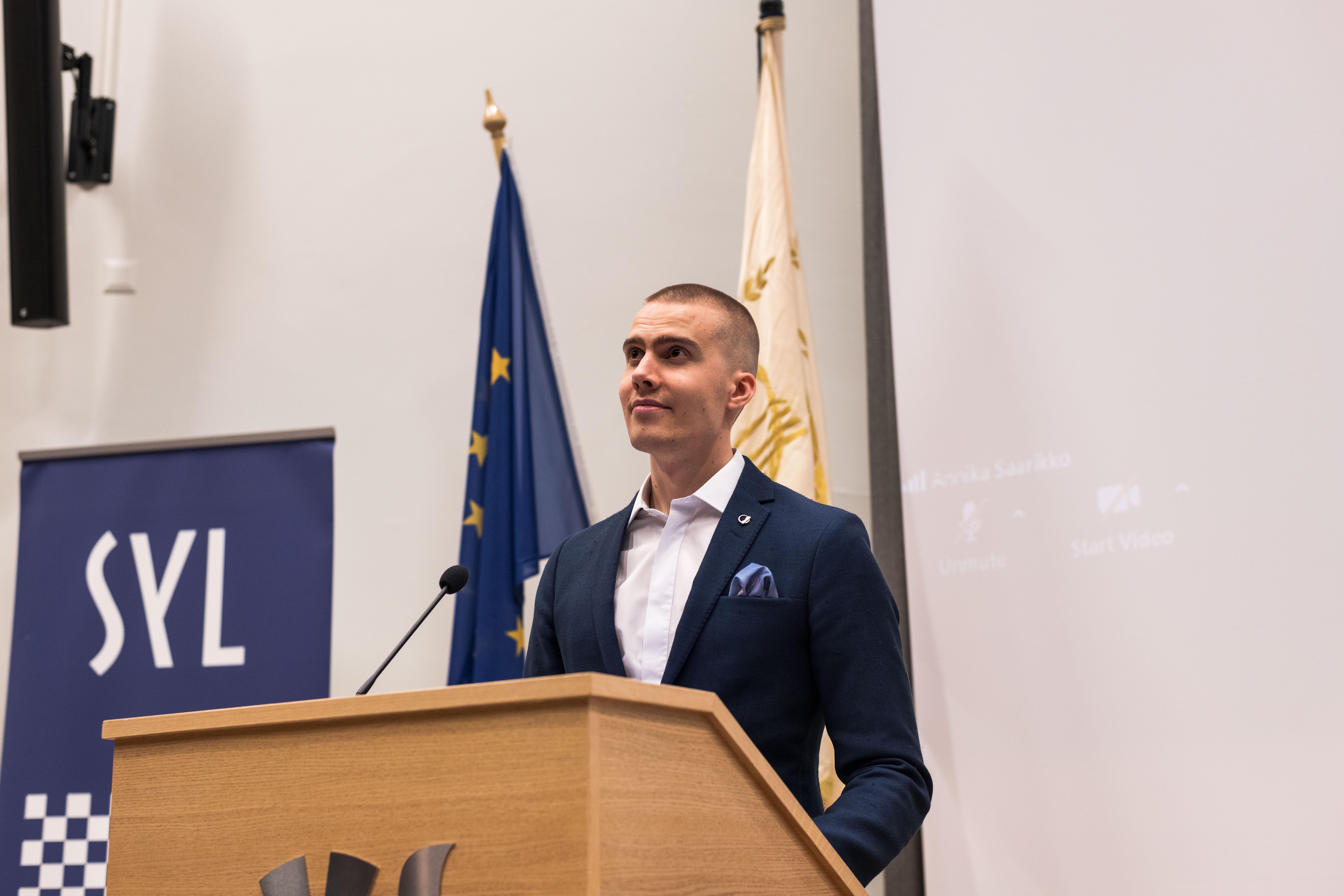 Kuvassa puheenjohtaja Tapio Hautamäki on puhujan korokkeella ja hän katsoo toiveikkaasti salin yläviistoon. Tapion takana näkyy SYL:n ja EU:n liput.