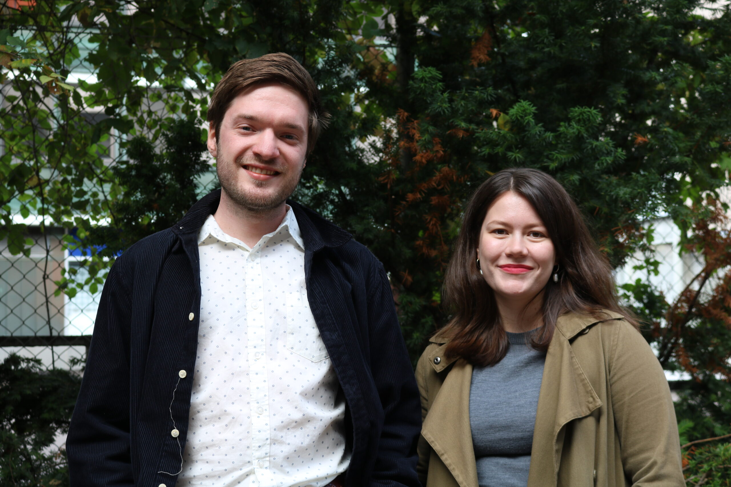 Yuri Birjulin ja Veera Alahuhta seisovat kuvassa vierekkäin vehreän pusikon edessä. Molemmat hymyilevät.